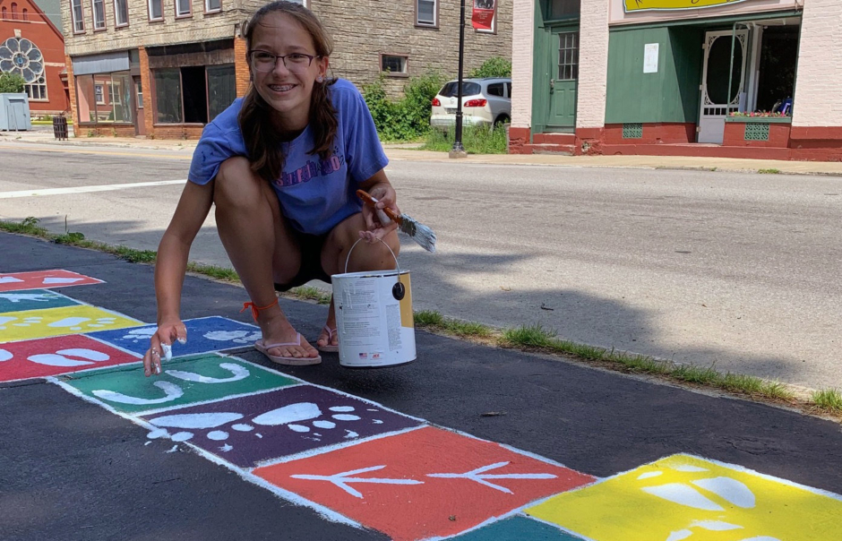 Ella Canella painting a street mural